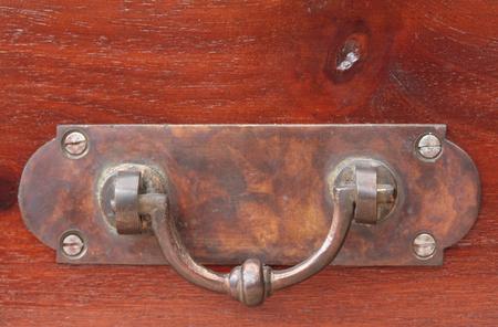 Een oud handvat op gelakt hout
