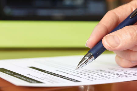 Hand with Pen Signing Form by Green Folder Stockfoto - 95392326