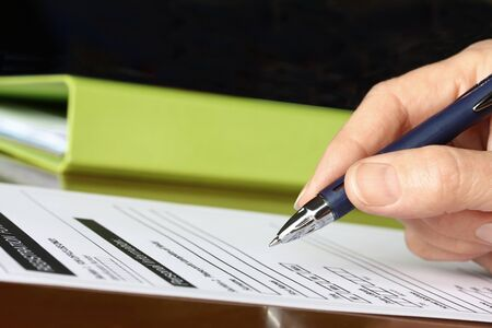 Hand with Pen Signing Form by Green Folder Stockfoto
