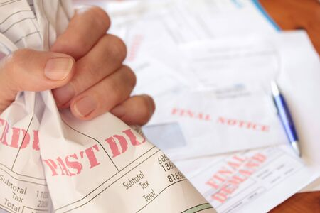 Crumpled overdue unpaid bills clutched in a hand in frustration Stockfoto - 95454514
