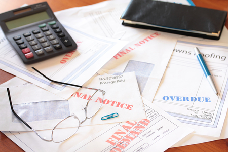 Overdue unpaid bills on table with calculator, spectacles and cheque book Stockfoto - 95456216
