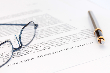 Fountain pen and blue spectacles resting on top of disclosure agreement Reklamní fotografie