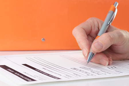 Hand with orange pen completing form on orange background