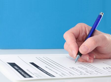 Hand with blue pen completing form on blue background Stockfoto - 95469366