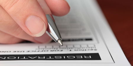 Closeup of a hand with a pen filling in a registration form