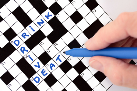 Hand completing crossword with Drink Drive Death message