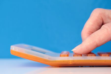 Fingers on an orange calculator closeup on a blue background 스톡 콘텐츠