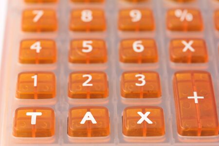 Taxation concept - Orange calculator with the word TAX added across the bottom 스톡 콘텐츠