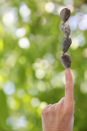 Hand with index finger balancing stones on blurred green background with copy space