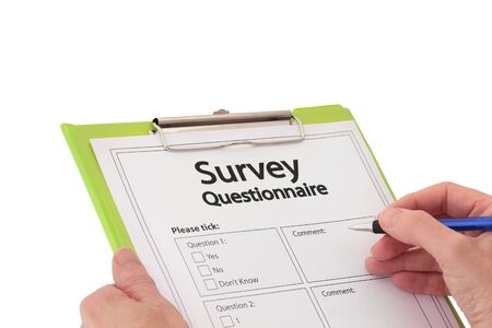 Hand with a pen filling out market research survey questionnaire on green clipboard