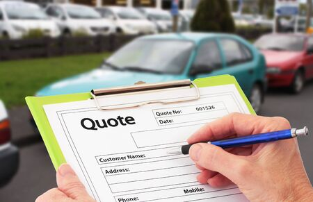 Hand with pen writing a quote or estimate for car repairs