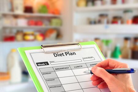 Hand with a pen completing a diet plan on a clipboard in front of an open fridge