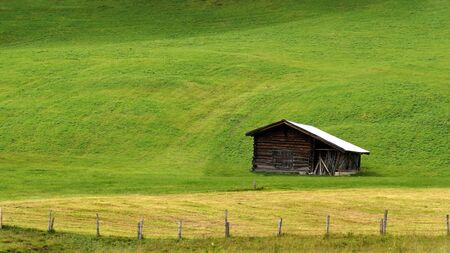 Barn for storing hay on a cow pasture in the mountains.