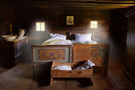 Old marriage bed, cradle, jug and bowl in a bedroom of a farmhouse.
