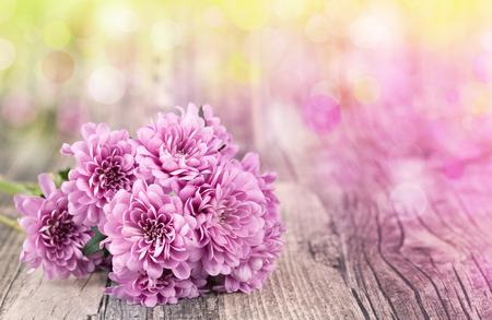 木製の背景にピンクの花、ボケ