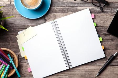 Lijst van het bureau met een kopje koffie een blanco notitieblok en een plant Stockfoto