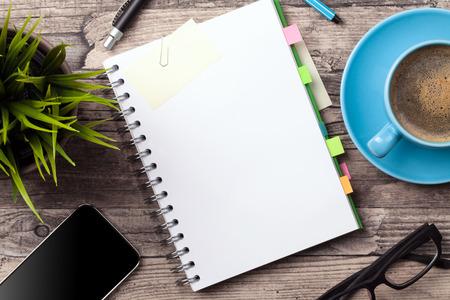 Vector de la oficina con una taza de café una libreta en blanco y una planta