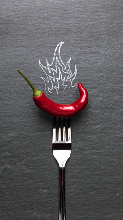red chili pepper with fire and a black graphite background