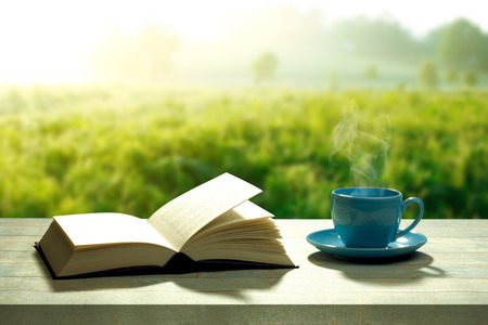 morning coffee: Open book with a coffee cup and a wooden table Stock Photo