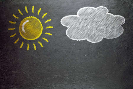 changing: sun and a cloud on a blackboard