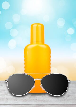 sun lotion: Sun Lotion with sunglasses and a beach background Stock Photo