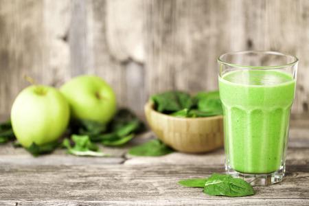 jugo verde: jugo de batido verde en mesa de madera con espinacas y manzanas