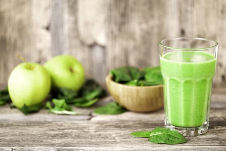 green smoothie juice on wooden table with spinach and apples