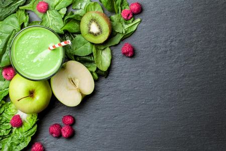 jugos: batido verde con las frutas y verduras en el fondo negro Foto de archivo