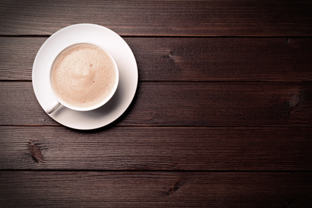 茶色の木製の背景の上にコーヒー カップ