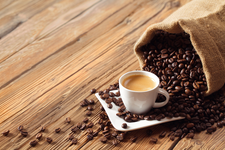 Coffee cup with coffee beans and wooden background