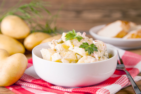 Potato salad on an old rustic wooden table Imagens