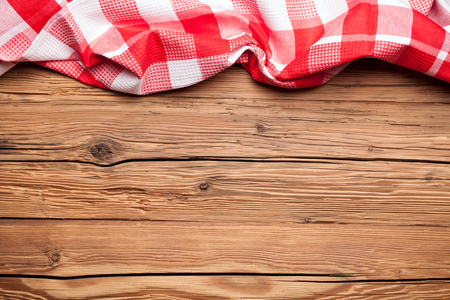 Checkered tablecloth on an old rustic wooden background