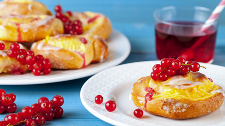 Puff pastry with pudding and red currants on a blue wooden table. Fruit cake.