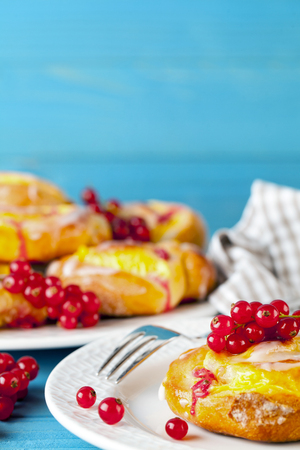 d0bb52624cc Puff pastry with pudding and red currants on a blue wooden table. Fruit  cake.