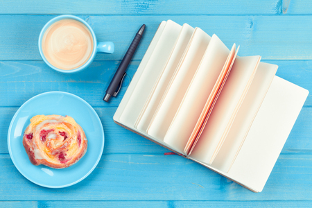 Coffee cup with a cake and open book on a blue wooden background