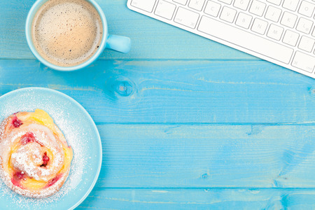 Coffee cup with a cake on a blue wooden table. Business background.
