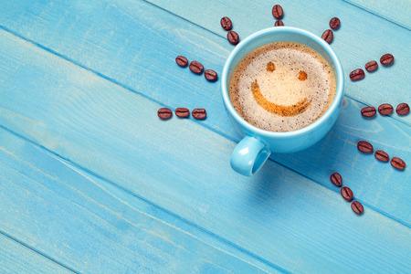 Taza de café con cara sonriente en la mesa de madera azul Foto de archivo