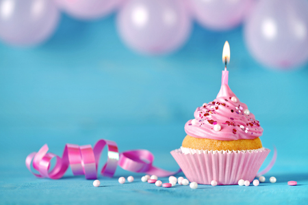 Happy birthday cupcake with candle. Pink birthday cake background with balloons.