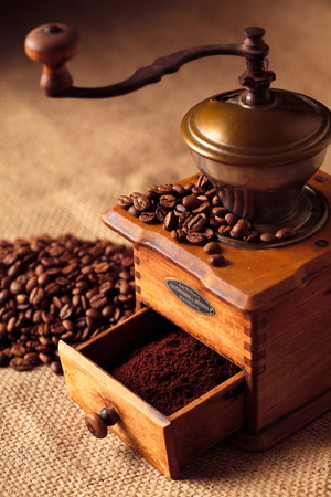 Coffee grinder with beans and coffee powder Imagens