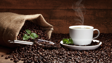 coffee cup with bean bag and leafs