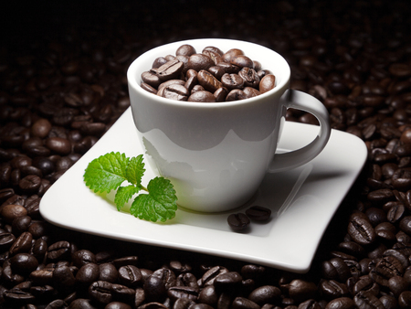 coffee cup with beans and a leaf