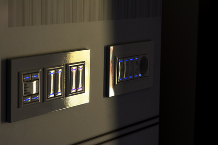 electricity providers: Light switch illuminated mounted on a panel