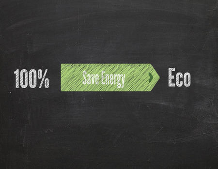 save heating costs: green arrow with text Save Energy on blackboard
