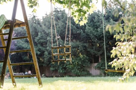 Children swing in the park with sunflare Banco de Imagens - 128839355