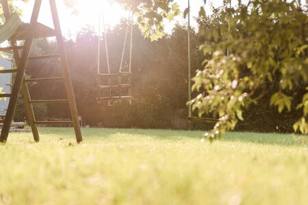 Children swing in the park with sunflare Banco de Imagens