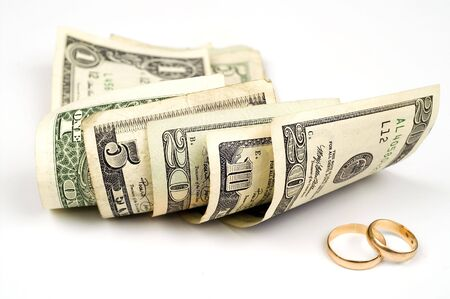 Dollars and wedding rings Stock Photo