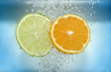 bubble acid: Lemon and tangarine slices in water with air bubbles on blue background. Stock Photo