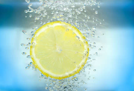 Lemon slice in water with air bubbles on blue background.