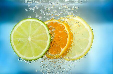 lemon slices: Mandarino calce e fette di limone in blu acqua con bolle d'aria.  Archivio Fotografico
