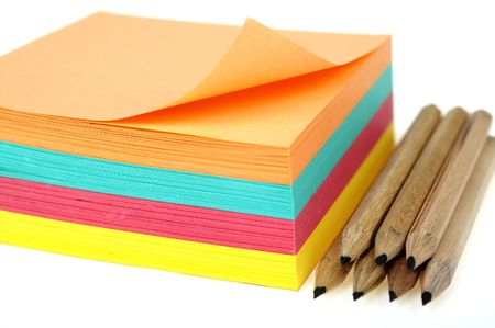 Stack of colorful post-it and pencils isolated on white